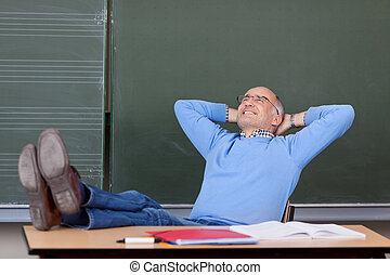 Professor With Hands Behind Head Looking Up At Desk -...