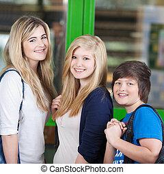 Happy Students Standing Against Door In School - Portrait of...