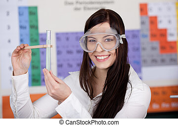 Female Student Holding Test Tube With Clamp In Classroom -...