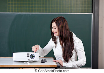Curious Student Touching Projector Against Chalkboard -...