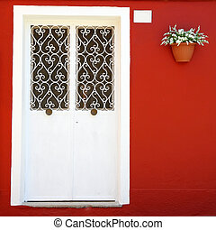 ornamental white double door and vivid red wall with hanging...