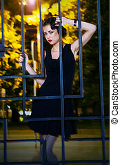 Pretty woman posing in cage outdoors at night - Emotions....