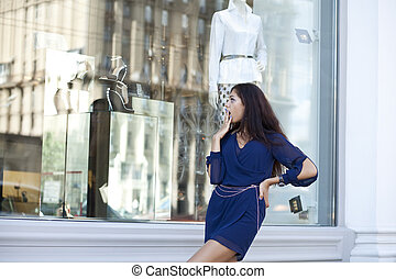 Young woman looking at shop window boutique