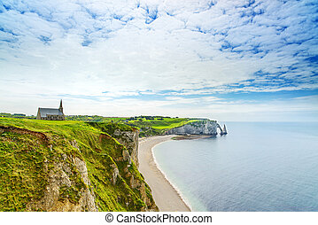Etretat, ocean, church and Aval cliff landmark. Normandy, France.