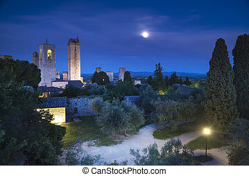 San Gimignano on night, medieval town landmark. Moon light on towers and park with cypress and olive trees. Tuscany, Italy, Europe.