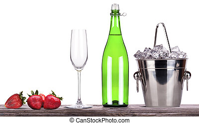 strawberry, ice bucket with champagne on a table -...