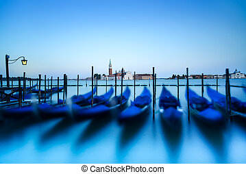 Venice, gondolas or gondole on sunset and church on background. Italy