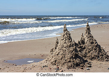 Sandcastle with twin towers on the beach against sea and...