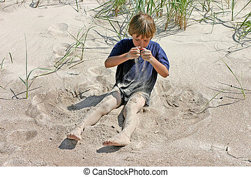 Pouring sand - 7-9 years old boy playing with sand on the...