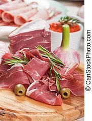 Prosciutto di Parma - Sliced prosciutto di Parma on wooden...