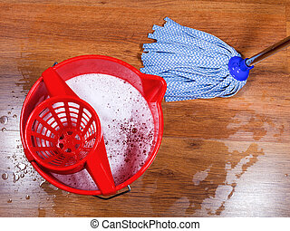 mopping of wooden floors - red bucket and mopping of wooden...