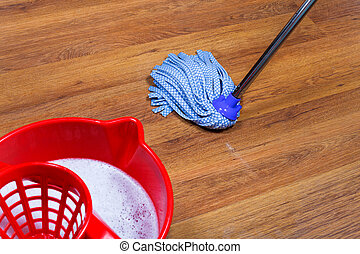 mopping of laminate floors - red bucket with water and...