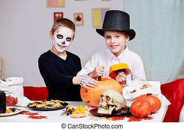 Cutting pumpkin - Photo of two eerie boys cutting holes in...