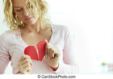 Suffering from love - Sad female tearing up red broken paper...