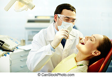 Checking up teeth - Young woman sitting in dentists chair...