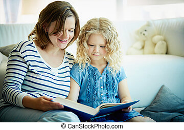 Reading tales - Portrait of cute girl and her mother reading...
