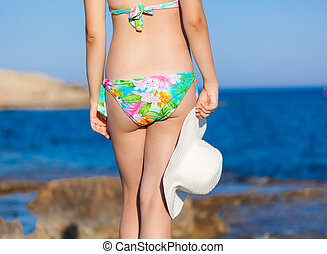 A woman with hat is on the beach