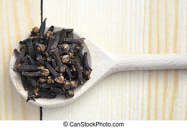cloves in a wooden spoon on white background