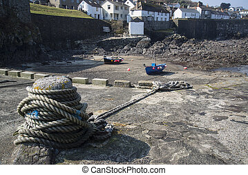 Harbour at low tide with fishing boats in old Cornish fishing village