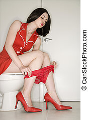 Woman sitting on toilet. - Caucasian young adult woman...