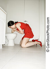 Woman vomiting in toilet. - Caucasian young adult woman...