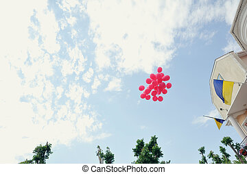 balloons - on cloudy sky flying red balloons and flag of...