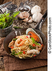 SpaghettiSeafood of topped with shrimp.