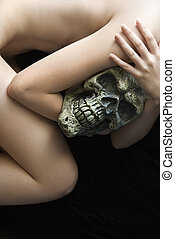 Nude woman with skull. - Nude Caucasian young adult woman...