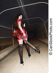 Woman walking with guitar.