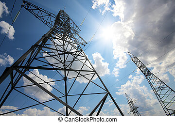 tall electric masts against sun and sky