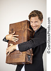 Young businessman embracing his old suitcase