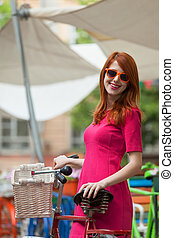 Redhead girl with bike at outdoor, city.