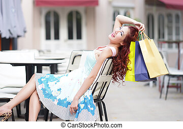 Young beautiful woman holding shopping bags - Young...