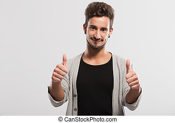 Happy young man - Handsome young man with thumbs up, over a...