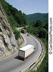 Trucks on mountain road - Trucks delivering cargo on...