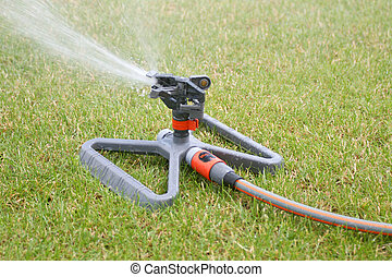 Lawn sprinkler spraying water over green grass at summer...