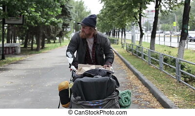 Belongings - Homeless man driving the cart with his...