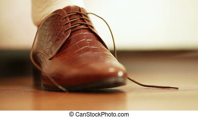 Tying shoelaces - Man tying shoelaces on expensive brown...