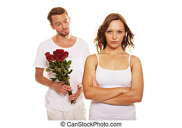 Husband offering a rose to his unhappy wife