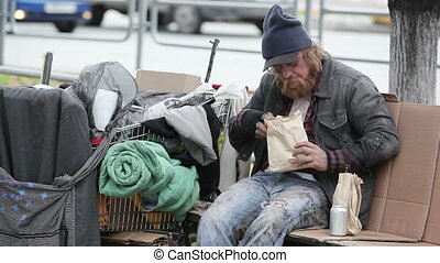 Lonely lunch - Hobo having a snack in the street with a...