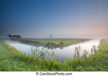 calm summer misty morning over river, Groningen, Netherlands