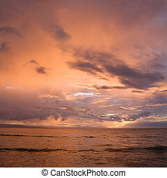 Maui sunset. - Orange glowing clouds during sunset on coast...