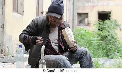 Booze and snack - Homeless man sitting on a porch of a...