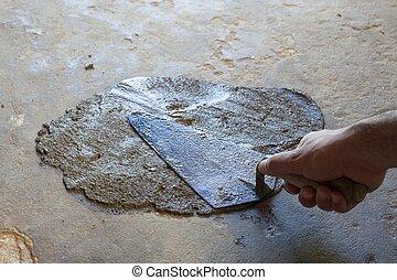 hand using trowel  with wet concrete floor