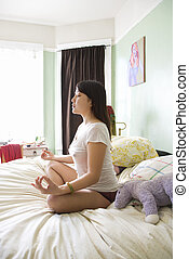 Young woman meditating - Side view of pretty Asian young...