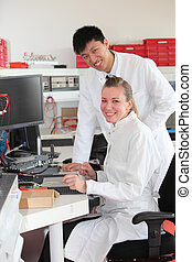 Two technicians at work in a laboratory with a young Asian...