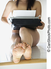Nude woman with typewriter. - Young nude Asian woman holding...