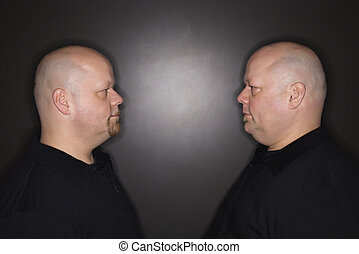 Twin men staring - Caucasian bald mid adult identical twin...