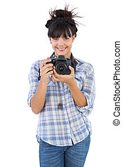 Young woman holding camera for taking picture