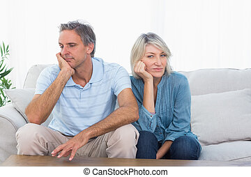 Couple not speaking after a fight at home on couch